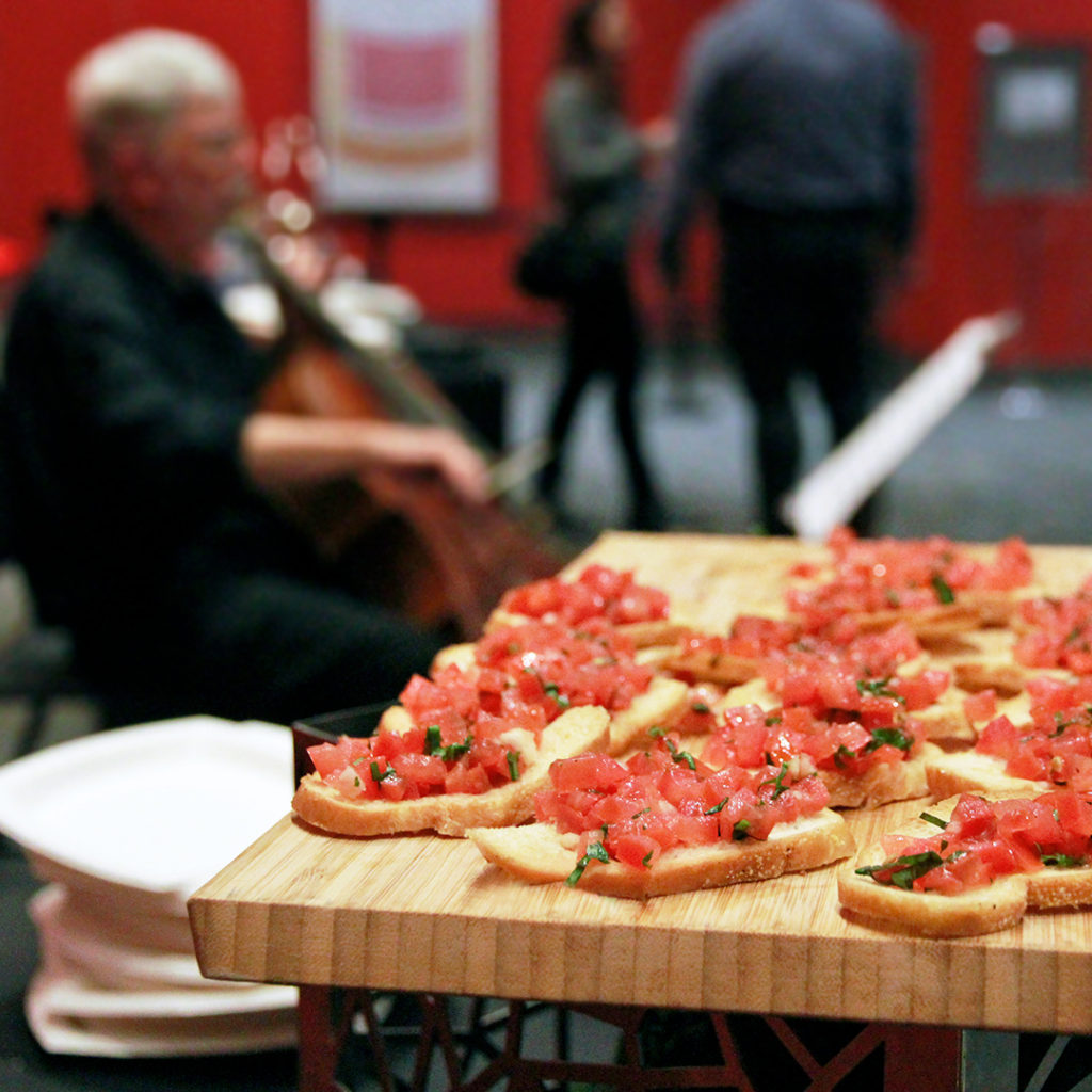 Bruschetta on crostini with man playing cello in background