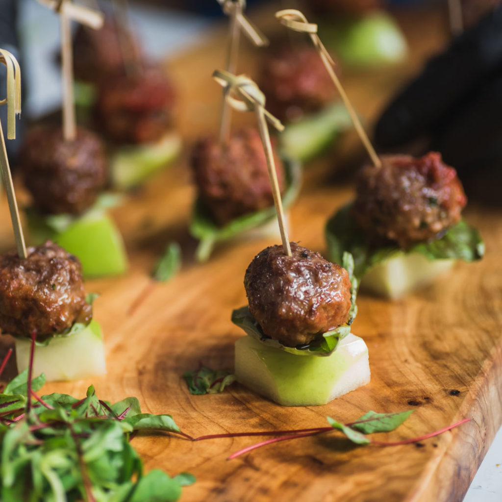 Kosher meatballs on apple chunks at a kosher event
